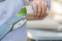 Worker Cutting Aluminum Rain Gutter With Heavy Shears