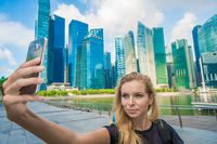 Tourist woman taking mobile phone selfie picture at Singapore cityscape