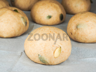 Pumpkin seed buns proofing on baking paper at close-up
