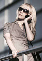 Young fashion business woman talking on mobile phone at office building