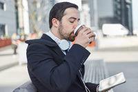 Geschäftsmann mit Tablet trinkt Kaffee