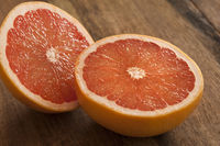 Pink grapefruit cut in half on wooden table
