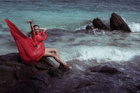 Woman in red dress on the rock