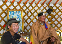 At the home of Mongolian herders, father and son in a in traditional yurt, Mongolia