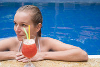 Woman with cocktail in the pool