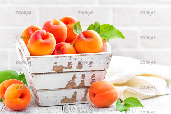Fresh apricots with leaves on white wooden background
