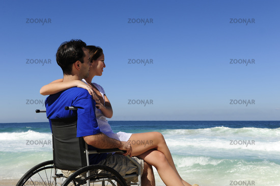 Couple on the beach, man in a wheelchair by the sea
