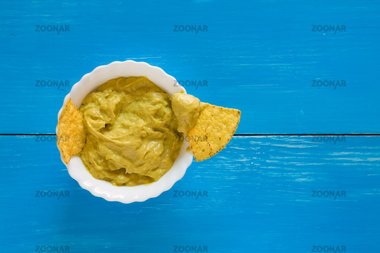 Nachos chips dipping in salsa guacamole over a blue background
