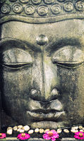 Buddha face statue with lotus flowers