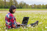 Woman sitting with laptop in spring meadow