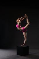 Redhead ballerina doing vertical gymnastic split