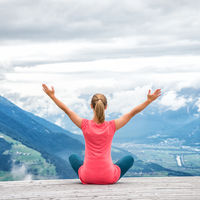 young woman meditate on top of the mountain