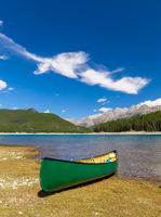 Green Canoe on the shore of a mountain lake