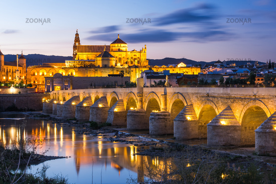 Illuminated Roman Bridge and Mosque-Cathedral at twilight in Cordoba, Spain