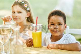 Afrikanischer Junge trinkt frischen Orangensaft