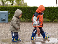 portrait of two male and female siblings, 3 and 5 years old, walking in a puddle