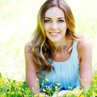 young woman in blue dress lying on grass