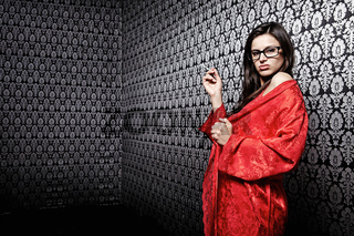 The attractive girl in red with a cigarette against a black wall with an ornament