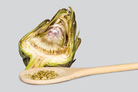 Artichoke cut in half and wooden spoon with fennel seeds