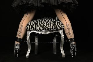 Frauenbeine in Zebra High Heels und Stuhl mit Kette gefesselt