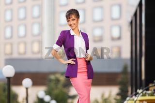 Young fashion business woman in purple blazer and pink skirt walking in city street