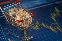 Bitcoin BTC coins in the shopping cart on the financial diagram. Cryptocurrency market concept.