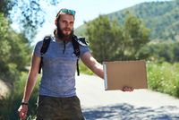 Hitch-hiking traveler with a blank cardboard sign