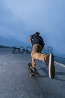Skateboarder pushing on a concrete pavement