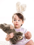 Baby girl playing with toy rabbit