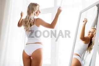 woman in underwear at mirror in morning