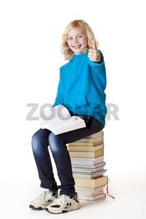 Glückliches Schulmädchen zeigt Daumen und sitzt auf Scholbüchern