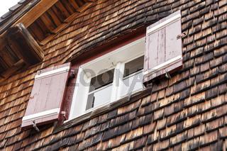 Das Fenster einer Berghütte mit Holzschindel- Fassade in den Alpen.