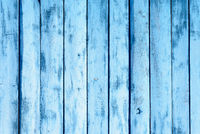 Blue painted wooden planks fading from the weather and effects of rain and sunlight.