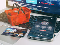 Mobile phone, shopping basket and credit card on laptop keyboard. Online shopping concept.