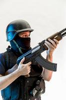 man armed with balaclava and bulletproof vest, gun and shotgun, kalashnikov