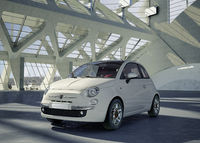 Fiat 500 city car, alone in the middle of a huge modern building environment.