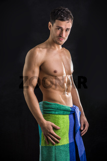 Naked young man with towel around his waist