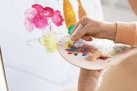 artist applying paint to palette at art studio