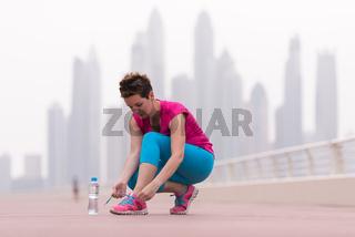 woman tying shoelaces on sneakers