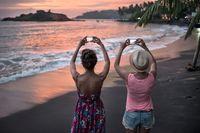 Girls photographing sunset on beach