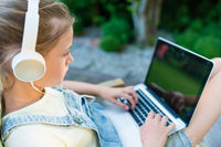 Closeup image of young girl watching video on laptop computer with blank copy space screen for your text message or information, female teenager holding open net-book on knees while sitting outside