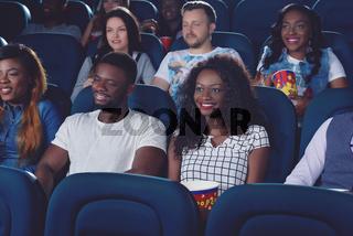 Friends watching movie in modern cinema hall.
