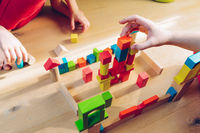 sisters have fun - playing with colorful wooden blocks - view from above