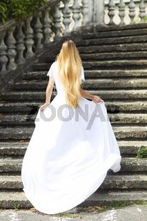 Beautiful running bride outdoors in park