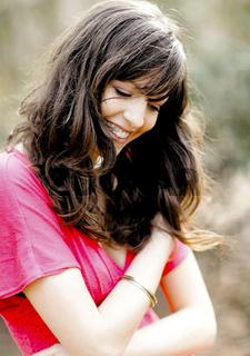 junge Frau mit braunen Haaren laechelt