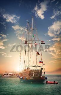 Wooden sailboat at sunset
