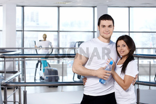 Happy young couple against training simulator in fitness club