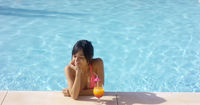 Contented woman at pool edge with drink
