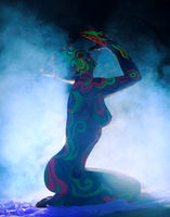 Side view of nude girl with body art in smoke