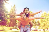 happy teenage couple having fun at summer park